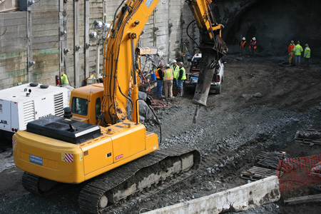 Excavator with jackhammer demolished the secant pile wall