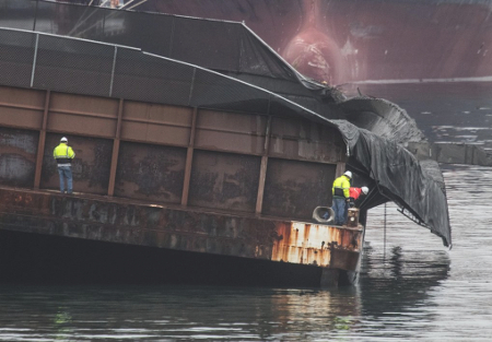 Workers examine the listing barge in Elliott Bay